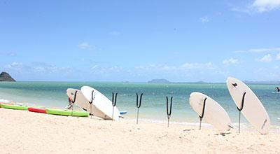 日差しが強い浜辺に、白いサーフィンボード