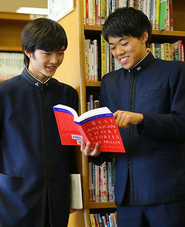 図書館で本を見ながら談笑する男子生徒二人