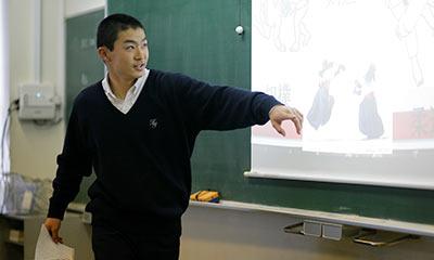 電子黒板の前に立ち、説明を行っている生徒。