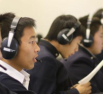 生徒がイアフォンを付け、オンライン授業中