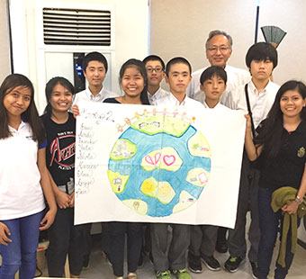 多国籍の海外修養生と共に。手には手描きの地球のイラスト。
