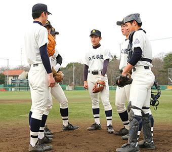 ピッチャーマウンドで円陣を組んで相談する野球部員