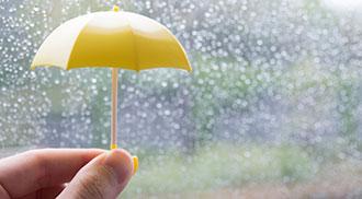 雫が付く窓ガラスの傍らに小指サイズの傘を持つ手